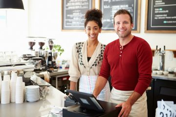 A café owner and worker standing by a cash register, smiling