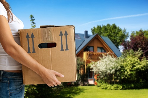 Woman carrying moving box with home in background